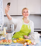 Girl with smartphone at kitchen Stock Images