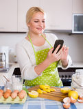 Girl with smartphone at kitchen Stock Photography