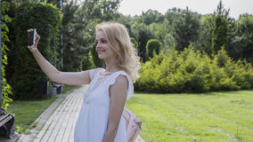 Girl with a smartphone. In the park Stock Photography
