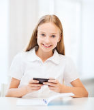 Girl with smartphone at school Stock Photography
