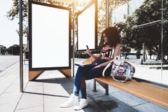 Girl with smartphone and two billboard templates in bus stop. A cheerful young caucasian woman with bulky curly hair is sitting on a yellow metal bench inside of royalty free stock photography