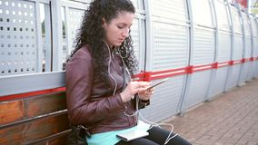 Girl with smartphone is waiting for train stock video footage