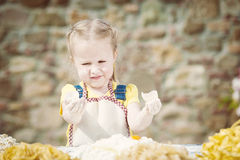 Girl smashing an egg into the flour for pasta. Royalty Free Stock Images