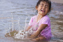 Girl is smashing water. The girl is smashing the sea water, splashes attack her back royalty free stock image