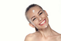 Girl smeared a cream face and smiles broadly. Stock Image