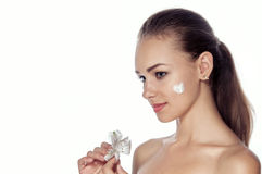 Girl smeared face cream. She is standing in profile and holding Stock Photo