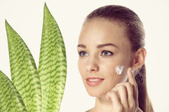 Girl smeared face cream. She is a three-quarters near the plant. Royalty Free Stock Photo