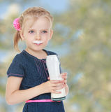 Girl smeared lips milk which she drinks out of a Royalty Free Stock Photography
