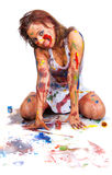 Girl smeared in paint. Covered in paint happy girl sitting on a floor Stock Photography