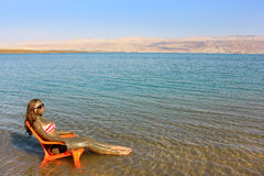 Girl smeared with therapeutic mud sunbathes, Dead Sea Stock Image