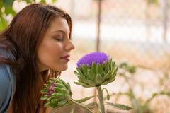 Girl smelling an artichoke flower Stock Image