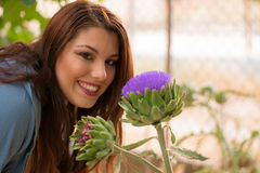 Girl smelling an artichoke flower Stock Photo