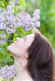 Girl smelling a  blooming lilacs Royalty Free Stock Images