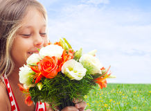girl smelling a bouquet on background of sky Stock Photography