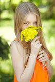 Girl smelling bunch of dandelions Royalty Free Stock Images