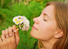 Girl smelling daisies Royalty Free Stock Photo