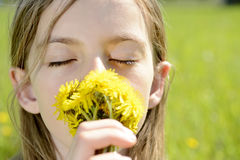Girl smelling dandelions Royalty Free Stock Images