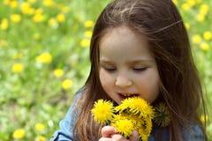 Girl smelling dandelions in spring Stock Photo