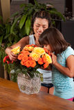 Girl smelling flowers. A young girl smells some fresh flowers while her mom looks on Royalty Free Stock Photo