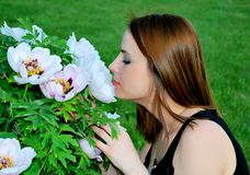 Girl is smelling flowers Royalty Free Stock Photography
