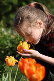 Girl smelling flowers in the garden Royalty Free Stock Photography