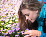 Girl is smelling flowers Stock Photos