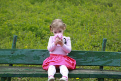 Girl smelling flowers, sitting on the bank in the garden Royalty Free Stock Photography