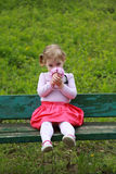 Girl smelling flowers, sitting on the bank in the garden Royalty Free Stock Image
