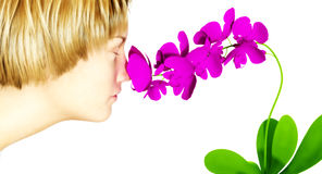 Girl smelling flowers. Woman taking time to stop and smell the orchids Royalty Free Stock Photo
