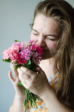 Girl smelling flowers. Young girls with flovers,  beautiful smile and eyes Royalty Free Stock Image