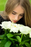 Girl smelling large bouquet of white roses, which Royalty Free Stock Image