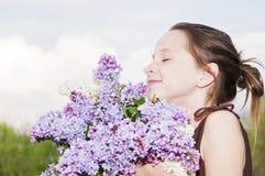 Girl smelling Lilacs Royalty Free Stock Photos