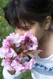 Girl smelling pink flowers Royalty Free Stock Photo