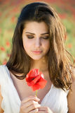 Girl smelling poppy Royalty Free Stock Photos
