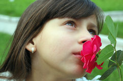 Girl smelling red flower Royalty Free Stock Photos