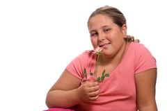 Girl Smelling A Rose. A young girl smelling a fresh rose isolated against a white background Royalty Free Stock Photo