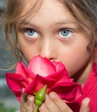 Girl smelling  rose. Little girl smelling  beautiful red rose Royalty Free Stock Photography