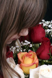 Girl smelling roses Stock Images