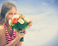 Girl smelling roses Stock Image