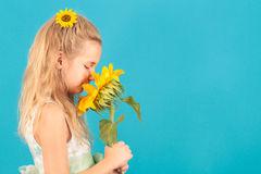 Girl smelling a sunflower Stock Photography