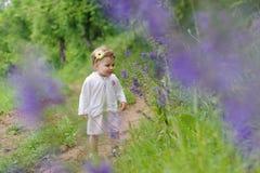 Girl Smelling Violet Flowers Stock Image