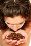 The girl smells aroma of coffee grains Royalty Free Stock Photos