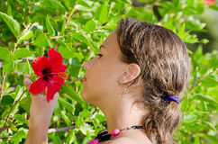 Girl smells an exotic flower Royalty Free Stock Image