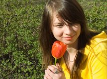 The girl smells a flower. The girl with a tulip royalty free stock images