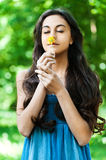Girl smells flower eyes closed. Young beautiful girl long hair summer park smells little yellow flower eyes closed royalty free stock photos
