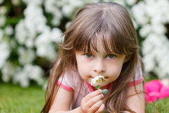 Girl smells on a flower otudoor in grass Royalty Free Stock Image