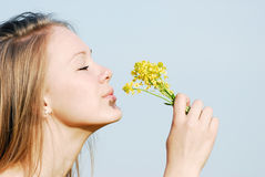 The girl smells flowers. The beautiful young woman inhales aroma of gentle yellow flowers Royalty Free Stock Images
