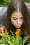 Girl smells flowers. Girl smells orange flowers in the garden Royalty Free Stock Photos