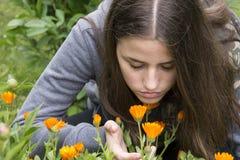 Girl smells flowers. Girl smells orange flowers in the garden Stock Photography