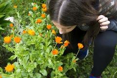 Girl smells flowers. Girl smells orange flowers in the garden Stock Photos
